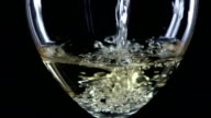 White wine is poured into a glass side view, black, closeup, slowmotion video