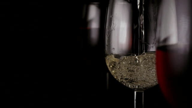 White wine is poured into one of the three glasses video