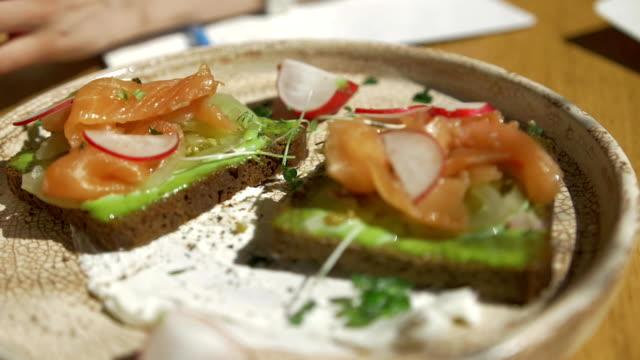 Whole grain bread with avocado paste and salmon breakfast concept video
