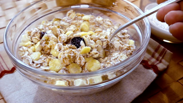 Whole grain cereal muesli in a bowl for a morning delicious breakfast with milk. Slow motion with rotation tracking shot. video