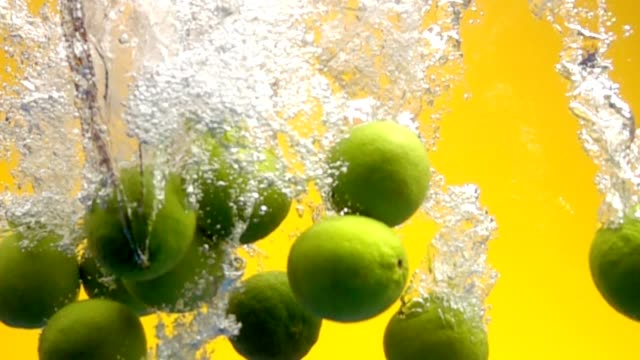 whole limes falling into water video