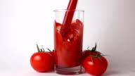 Whole red ripe tomatoes with leaves and tomato juice being poured into glass video