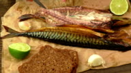 Whole smoked fish (mackerel) on a dark wooden table video