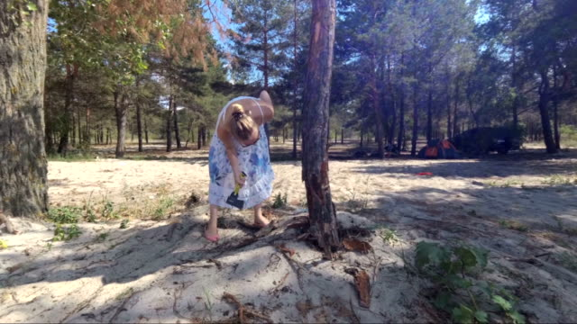 Wicked girl, chills her fervor about a dried tree. Slow motion video