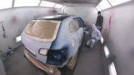 Wide angle footage of a car being painted and varnished in a painting chamber video
