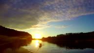 Wide beautiful river at sunset, tourists paddling boat. Slowmo video