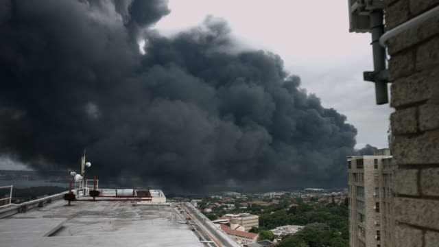 Wide of rooftop building with black smoke over the city. video