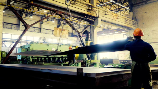 Wide sheets of metal are braided in big rolls at plant, time lapse video