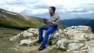 wide shot of man on a mountain using modern technology video