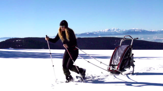 HD Wide Shot of Young Women Pulling Ski Trailer on Snowscape video