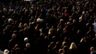Wide shot showing a multi ethnic cross-generation anonymous crowd beautifully lit by rim directional sunlight video