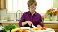 wide shot woman cutting peppers video