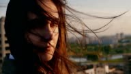 Wind blows long dark hair. girl standing on the roof smiling, looking at the camera. close up. Slow motion video