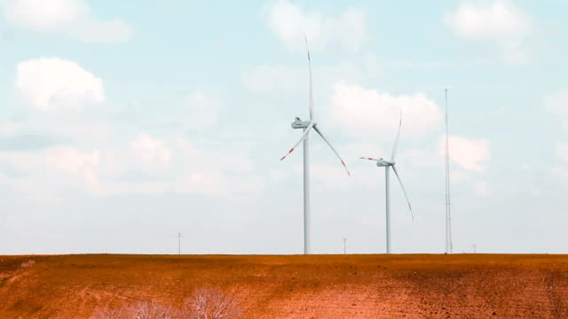 wind energy turbines, renewable electric energy source, under blue sky with white clouds video