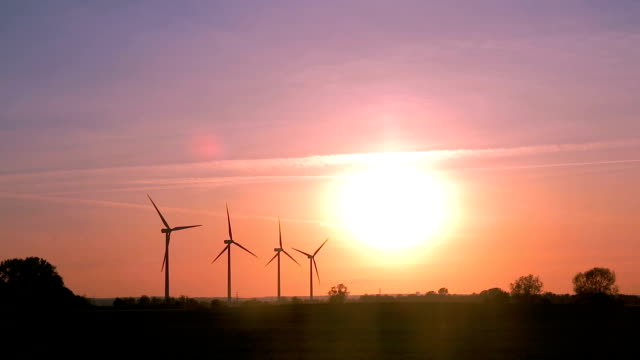 Wind farm on a field during sunset with colorful sky. Sustainable living or energy abstract concept. video