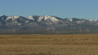Wind farm turbines spin on snowy Abajo Mountains Monticello Utah video