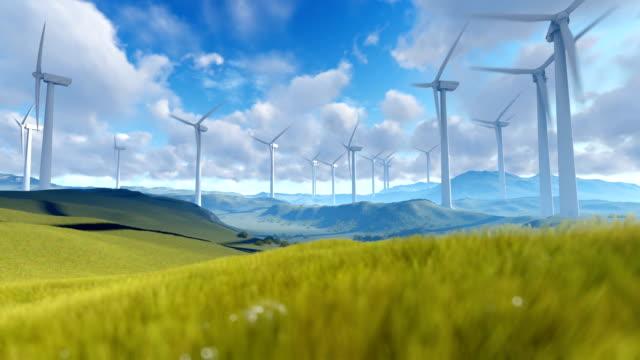 Wind turbine farm over green meadow against cloudy sky video
