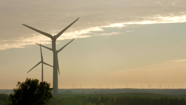 Wind turbine farm with rays of light at sunset video