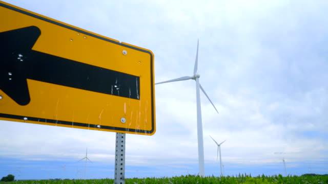 Wind turbine generator on green farm field. Road sign pointing on wind turbines video