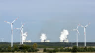 Wind turbines in front of a coal-fired plant video