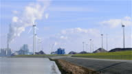 EEMSHAVEN, THE NETHERLANDS - CIRCA FEB 2016: Wind turbines near traditional energy plant video