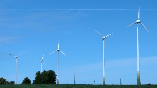 Wind turbines on the field against clear blue sky video