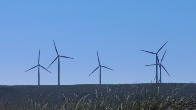 Wind turbines with blowing grass in foreground video