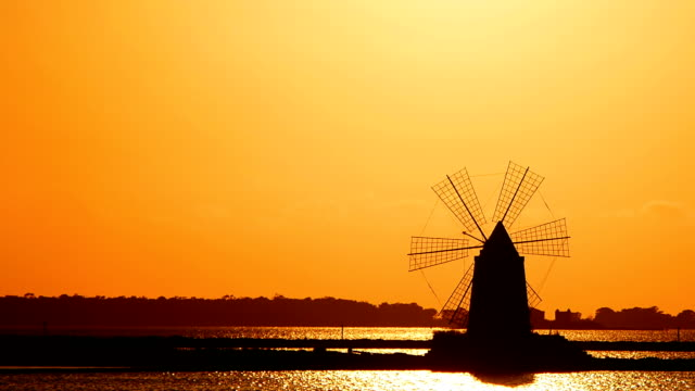 windmill at sunset: sky, sun, yellow, salt pans of Trapani, Sicily, Italy video