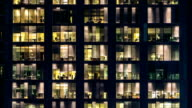 window of the multi-storey building of glass and steel lighting and people within timelapse video