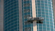Window washers moving up a skyscraper video