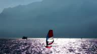 Windsurfer on lake wave under sunlight, Italy video