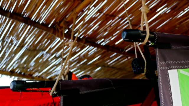 Windsurfing gear hanging on a sea beach video