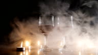 Wine glasses and burning candles in the smoke video