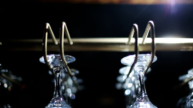 Wine glasses hanging from a rack video