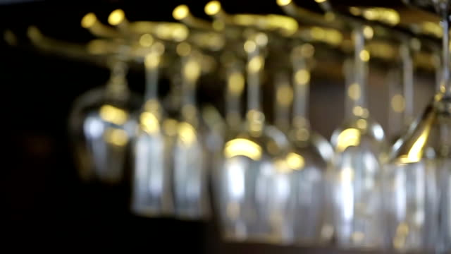 Wine Glasses hanging from a rack. video