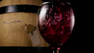 Wine is poured into a glass on the background of a barrel. Slow motion video