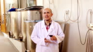 winemaker in lab coat examining sample of wine video