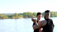 Wing Chun art by master and follower near the river. Slowly video
