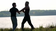 Wing Chun performance near the river between strong men. Slowly video