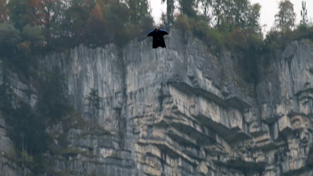 Wing suit flier descends from cliff, aiming for valley below video