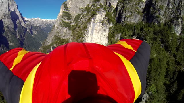Wing suit flier descends from mountain cliff video