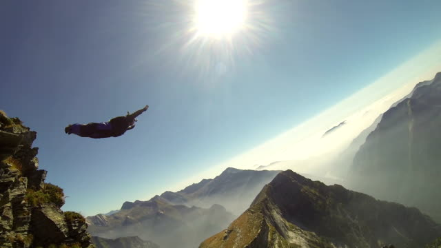 Wing suit flier descends from mountain ridge crest, sunshine video