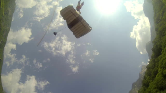 Wingsuit flier lands with parachute in mountain meadow video
