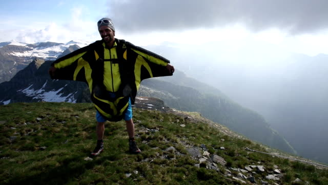 Wingsuit flier poses on mountain summit, spreads wings video