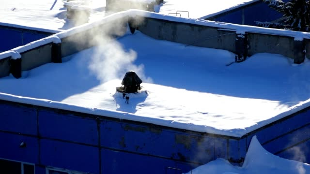 Winter background  the roof of a modern building covered with snow, smoke coming from the chimney, video