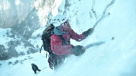 SLO MO winter climber using ice axe to go uphill video