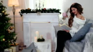 winter holidays, girl reading a book, woman drink tea from a cup, in cozy clothes, sitting by the fireplace with candles near the decorated Christmas tree video