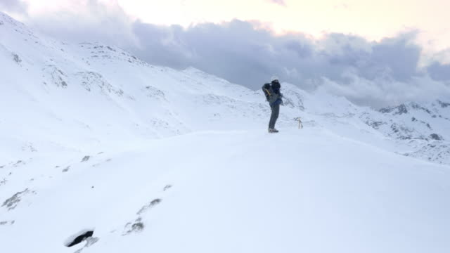 AERIAL Winter mountaineer putting on a backpack on mountain top video