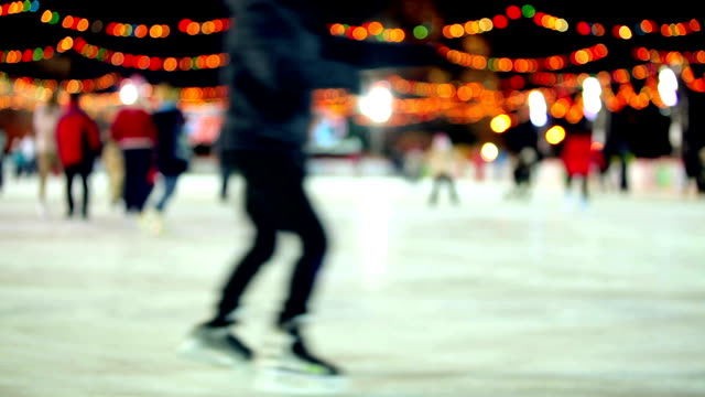 Winter outdoor ice skating with Christmas lights & people at night video
