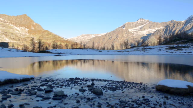winter river flowing to frozen mountain lake in italian alps video
